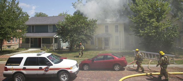 Smoke pours out of a roof vent as firefighters work their way inside 1030 Ohio during a two-alarm house fire Saturday afternoon.