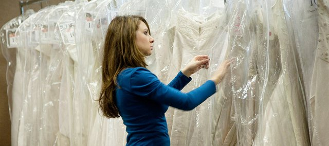 A bride-to-be sorts through dresses at a past event for the Nationwide Tour of Gowns, which comes to the greater Kansas City area this weekend.