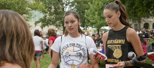 Haskell Indian Nations University freshmen Kelia Keams, Shiprock, N.M., left, and Mariah Watchman, Pendleton, Ore., pick up a few free school supplies at a Back2Campus outreach event on campus Sunday. Students also enjoyed a cook-out and music.