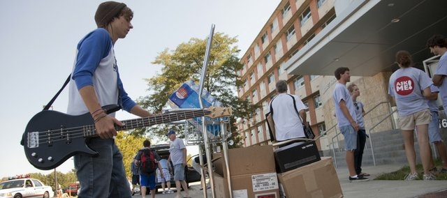 Luke Clark, Olathe, carries his bass guitar and pushes some belongings into his residence hall Sunday morning, August 15, 2010. This coming week is Hawk Week and will feature several activities each day for KU students.