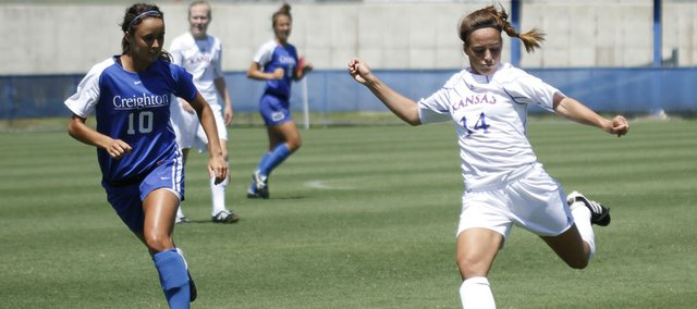 Kansas University's Madi Hillis (14) takes a shot as Creighton midfielder Laura Nasseri closes in on the play. Creighton won an exhibition with the Jayhawks, 3-0, Sunday at the Jayhawk Soccer Complex.
