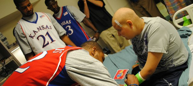 Kansas' Marcus Morris autographs the cast of a Children's Mercy Hospital patient as teammates Markieff Morris (21) and Mario Little wait their turn. The Jayhawks visited the Kansas City, Mo., hospital on Wednesday.