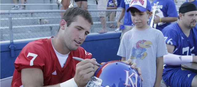Kansas quarterback Kale pick, left, signs a helmet for Ryan Mata, 8, of Liberty, Mo., during Sunday's Fan Appreciation Day at Memorial Stadium. About 500 fans attended the event.