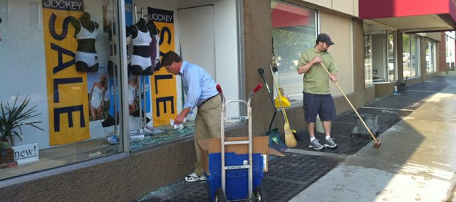 Weaver's vice president Earl Reineman, left, cleans up broken glass with the help of an employee after a deer jumped through a display window at the store, located at 901 Massachusetts St., early Monday morning.