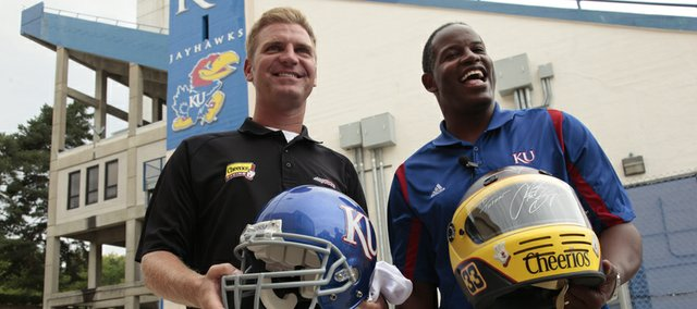NASCAR driver Clint Bowyer exchanges helmets with Kansas football coach Turner Gill during a tour of the Anderson Family Football Complex on Tuesday.