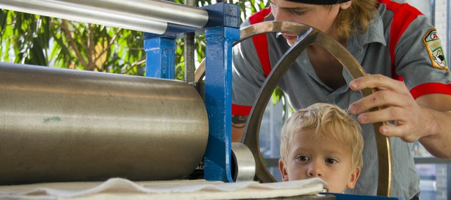 Elliot Ahlvers, 5, Lawrence, watches as Logan Lippincott turns the wheel of a print press during a printmaking demonstration held inside the Lawrence Arts Center during the first Final Fridays event. The event staged art exhibits at several locations downtown.