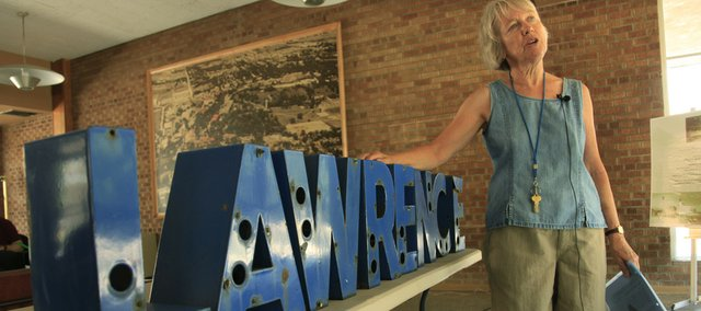 Carey Maynard-Moody, president of the Depot Redux group, talks Saturday about the return of the Lawrence sign that was stolen from the Burlington Northern Santa Fe depot.