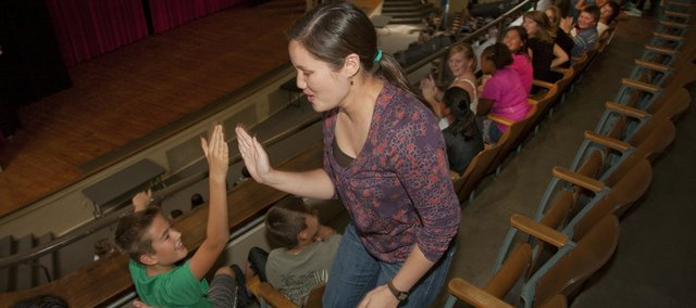 Central Junior High mathematics teacher Jennifer Clarkson gets high fives from students Seth Winchester, left, and Roscoe Bradt after it was announced Tuesday that she was awarded a Lawrence Horizon Award during a school assembly.