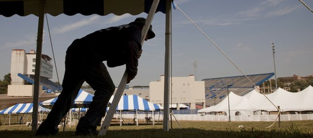 Arnulfo Guardado, an employee with All-Seasons Rental in Grandview, Mo., raises one of multiple tents Tuesday on the hill south of Memorial Stadium in preparation for Kansas University's first football game of the season. The Jayhawks  will play North Dakota State at 6 p.m. Saturday. Downtown Lawrence will be the site of a Jayhawk football fan pep rally Thursday night.