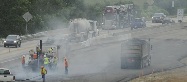 Crews continued repaving work on the Kansas Turnpike east of Lawrence on Thursday. Reduced lanes on the turnpike because of ongoing road construction will be just one of the hurdles facing motorists traveling to Saturday's football season opener at Kansas University. Labor Day travelers, a 2:30 p.m. football game at Kansas State University and opening weekend of the Renaissance Festival could also add to Saturday's traffic headaches on Interstate 70.