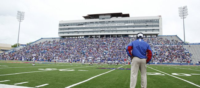 New Kansas University coach Turner Gill watches the first half of the April 24 spring game at Memorial Stadium. A considerably larger crowd  featuring his parents  is expected today for his first real game as the Jayhawks head coach.
