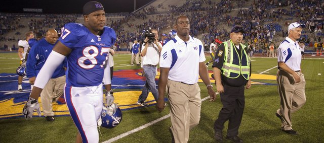 Head coach Turner Gill purses his lips as he makes his way from the field alongside tight end Bradley Dedeaux (87) and defensive coordinator Carl Torbush following the Jayhawks' 6-3 loss to North Dakota State, Saturday, Sept. 4, 2010 at Kivisto Field.