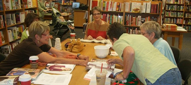 Ruby Shade, from left, Charlotte Ikenberry, Betty Loucks, Sherri Meredith and Wendy Pinne, all of Lawrence, gather around the latest knitting magazine Shade purchased during their meeting in Borders. They're among an informal group of knitters who gather Saturdays at Borders, 700 N.H.
