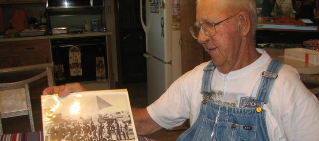 Harry Kelley, of Basehor, flips through a scrapbook displaying a photo of him and other World War II prisoners of war in Cairo, Egypt, after they were released at the end of the war. Kelley said one other person in the photo was still alive. Kelley will celebrate his 90th birthday at 3 p.m. today at the Basehor VFW post.