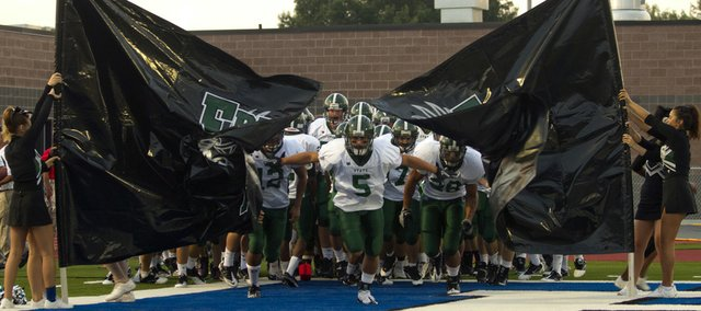 Free State senior running back Preston Schenck (5) leads the Firebirds onto the field against Leavenworth. The Firebirds led the Pioneers, 27-7, in the second quarter on Friday when severe weather postponed the game at Leavenworth.