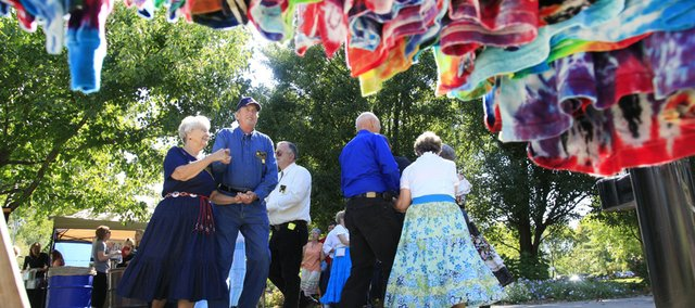 A rack of tie-dyed t-shirts hangs in the foreground as, from left, Betty Alexander and Larry Demoss, both of Lawrence, lead the Happy Time Squares square dancers at the Fall Arts and Crafts Festival in South Park.