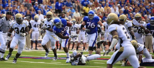 Kansas running back James Sims, center, avoids a tackle as he charges up-field against the Georgia Tech defense. Sims rushed for 101 yards in his collegiate debut Saturday, helping KU stun the Yellow Jackets, 28-25, at Memorial Stadium.