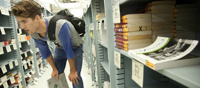 Kansas University fifth-year senior Vance Carlson, of Belleville, searches for a design textbook Friday at the Kansas Union Bookstore. Students now have the option of renting textbooks from the bookstore as it tries to keep up with online competition.