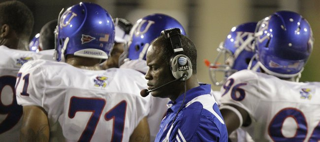 Kansas head coach Turner Gill closes his eyes as he paces past his pl