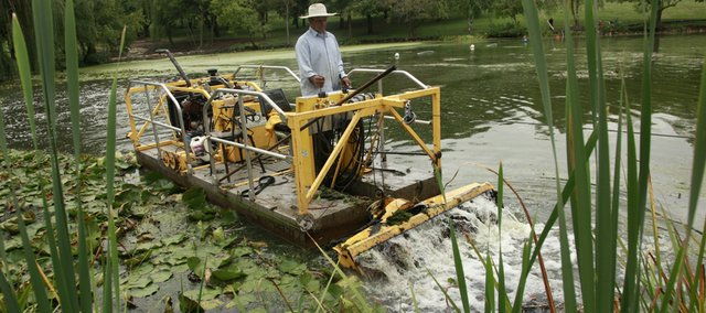 Selvine Calix, who works for Stream, Lake and Wetland Solutions of Kansas City, Mo., works a small dredger on Thursday  that helps take the silt out of Potter Lake on the Kansas University campus. The silt is pumped into a giant bag that holds the sediment until it's trucked away.