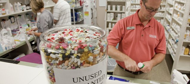 Pat Hubbell, pharmacist and owner of Sigler Pharmacy, fills out a prescription order Sept. 21, 2010, near a large jar of discarded medicine. The collection amounted to about six months of unused medications dropped off at Sigler Pharmacy, 4951 W. 18th St.