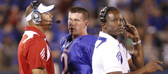 Kansas coach Turner Gill, right, quarterback Jordan Webb, center, and Joe Dailey, KU's on-campus recruiting coordinator, come together on the sideline during Kansas' Sept. 4 game against North Dakota State. Dailey had been signalling in plays on the sideline for KU's first two games, a violation of NCAA rules the Jayhawks rectified in their third game.