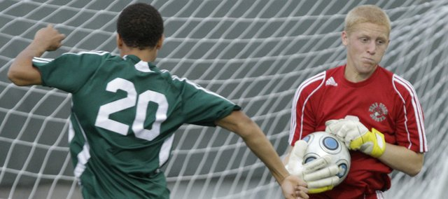 Free State soccer goalie Elliott Johnson, right, makes a save on a Shawnee Mission South goal attempt. The Firebirds lost, 1-0, in overtime Thursday at Free State High.