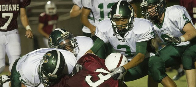 A pack of Free State high defenders brings Shawnee Mission North running back Kendall Kelly (3) to the ground. Free State routed SM North, 46-7, on Friday in Overland Park.