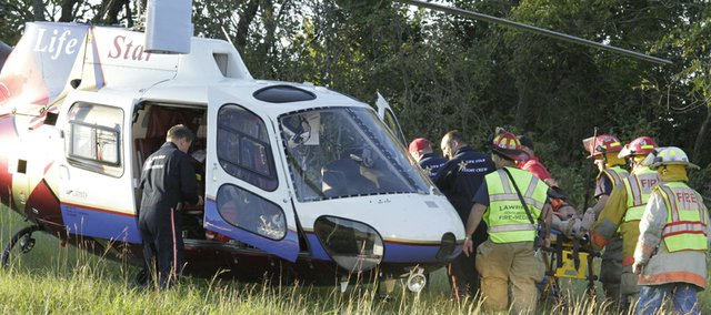 Emergency crews load an accident victim onto a LifeStar helicopter to be transported to an area hospital. The man was the driver of a jeep that rolled over on the Farmers' Turnpike between Lawrence and Lecompton.