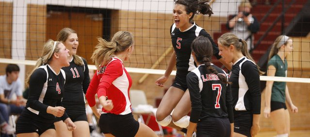 Lawrence High players Morgan Green (4), Kailey Wingert (11), Kendyll Severa, in red shirt, Caitlin Broadwell (5) Kelsey Broadwell (7) and Krista Costa celebrate a point against Free State. The Lions beat the Firebirds, 2-1, in a triangular Thursday at LHS.