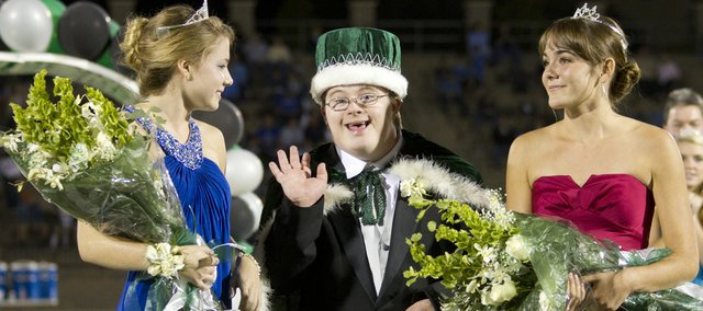 Owen Phariss waves to the crowd after being crowned homecoming king during halftime of Free State's football game Friday night. Audrey Hughes, left, and Rachel Heeb, right, tied for homecoming queen honors. Free State lost the football game to Shawnee Mission East, 28-21.