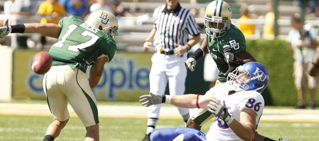 Kansas tight end Tim Biere falls backwards after colliding with Baylor safety Mike Hicks (17) during the fourth quarter Saturday, Oct. 2, 2010 at Floyd Casey Stadium in Waco, Texas. At right is Baylor defensive back Mikail Baker.