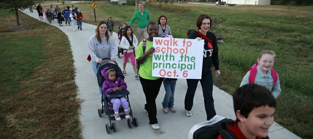 From left, Nancy Rothwell pushes her daughter Gladys Demby as New York student Rachel Atkins holds a sign with New York Principal Nancy DeGarmo as students and parents walked from the Boys and Girls Club on Haskell to New York School. Wednesday, Oct. 6 was International Walk to School Day.