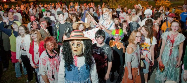 Zombies gather for instructions before making a scary stumble along Massachusetts Street Thursday night, Oct. 7, during the fourth annual Lawrence Zombie Walk. Participants were asked to bring donations for the Humane Society, local food banks and homeless shelters.