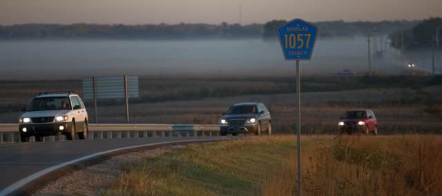 Morning commuters drive out of a thick fog between Eudora and Lawrence on Tuesday. About 20,000 Douglas County motorists commute into Kansas City each day. If Lawrence is determined to be out of compliance with Environmental Protection Agency regulations, all gasoline stations in Douglas County likely would be required to sell specially formulated, low-vapor gasoline during the summer months.