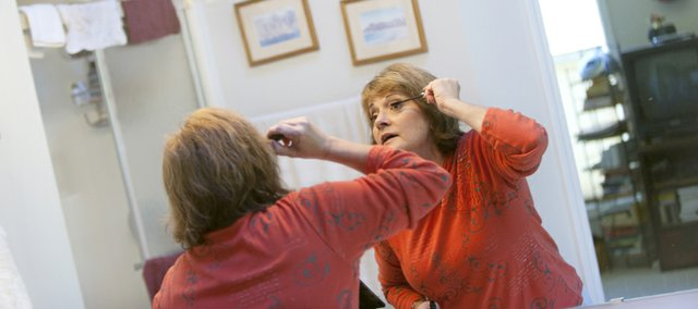 Sandy Cooper, a Lawrence Mary Kay representative, applies mascara Wednesday at her home.