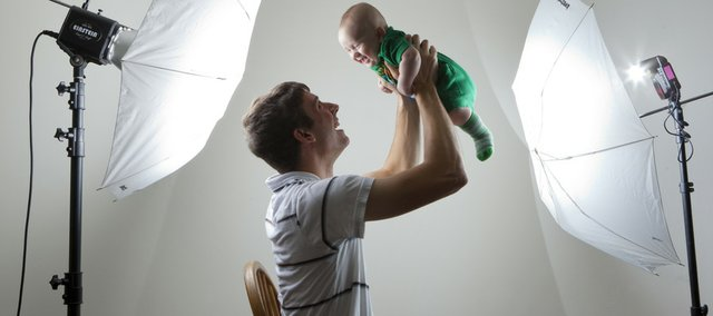 Lawrence portrait and wedding photographer Adam Buhler is pictured with his 3-month-old son, Everett, in his Lawrence home. For nice candid photographs, Buhler suggests paying close attention to your children's interests and then photographing them participating in the activities.