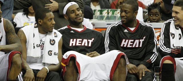 Mario Chalmers and LeBron James rest on the bench late in the fourth quarter during preseason NBA action.