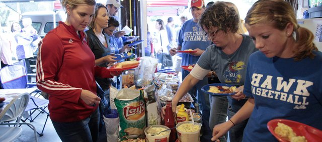 Tailgaters get food inside a garage on Ninth and Illinois streets that provides cover on a rainy Saturday last month before the New Mexico State game at Memorial Stadium.