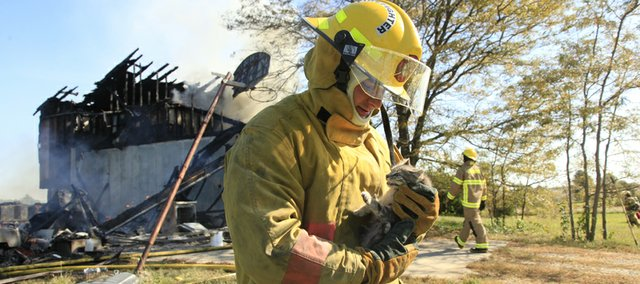 A firefighter holds a small cat that ran from a fire in the 200 block of US Highway 40 Thursday Oct. 14, 2010. Several area township fire departments were called to the scene of a house fire in western Douglas County about 11:30 a.m. All of the home's occupants escaped, but the home is believed to be a total loss.