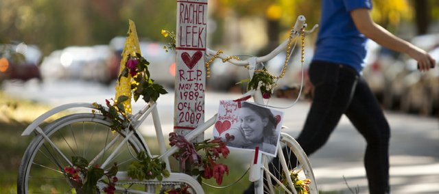 "A pedestrian crosses the street behind a ""ghost bike"" placed near the intersection of 10th and Tennessee streets in memory of Rachel Leek, a Lawrence resident who was killed while riding her bicycle as a result of a hit and run accident near the spot in the early morning hours of Oct. 16, 2009."