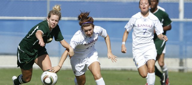 Kansas midfielder Caroline Kastor (center) competes for control of the ball with Baylor defender Hannah Dismuke, left. Baylor beat KU, 1-0 in double overtime, Sunday at the Jayhawk Soccer Complex.
