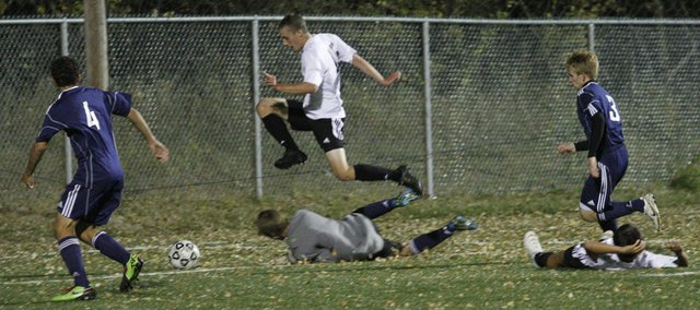 Free States Alec Heline, top, jumps over the Mill Valley goalie in the first overtime. The Firebirds tied Mill Valley, 1-1, on Monday at Free State.