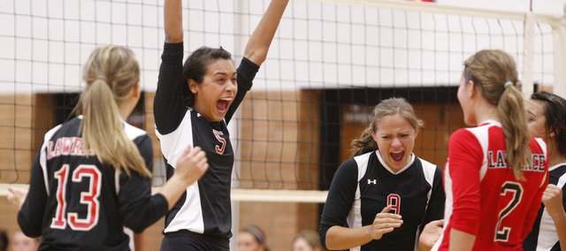 Lawrence High senior Nicole Bostick (13), freshman Caitlin Broadwell (5), sophomore Krista Costa (9), senior Kelsey Broadwell and senior Kendyll Severa (2) celebrate the Lions' sweep of Emporia High. The Lions also lost to Blue Valley North in their triangular on Tuesday at Lawrence High.