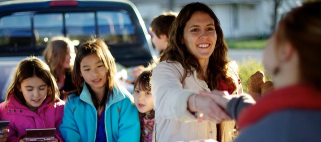 "Megan Paisley of Crane River Farm, greets Camillle Cody while the ""market kids"" play in the back of Paisley's truck during the season's first Downtown Lawrence Farmers' Market on April 10. Paisley is part of a growing trend of female farmers, which now account for an estimated 30 percent of farmers in the US."