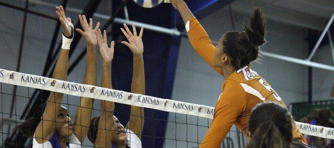 Kansas players Tayler Tolefree, left, and Karina Garlington rise up to get a block on Texas player Rachael Adams. The Jayhawks lost to the Longhorns, 3-0, on Wednesday at Horejsi Center.