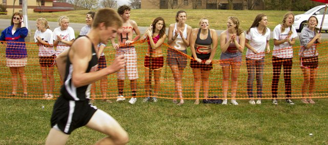 Lawrence High cross country runner Gavin Fischer heads to the finish line as some of his classmates cheer him on during the 6A regionals cross country meet held Saturday afternoon at Haskell Indian Nations University. Fischer finished in sixth place with a time of 17:00.08.