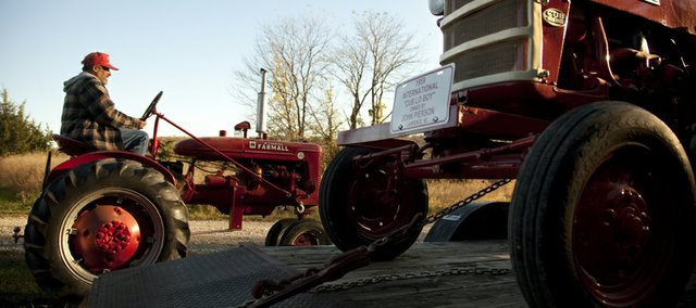Richard Runnebaum, of Berryton, drives a tractor to be loaded on a trailer and transported to Gardner for the sale.
