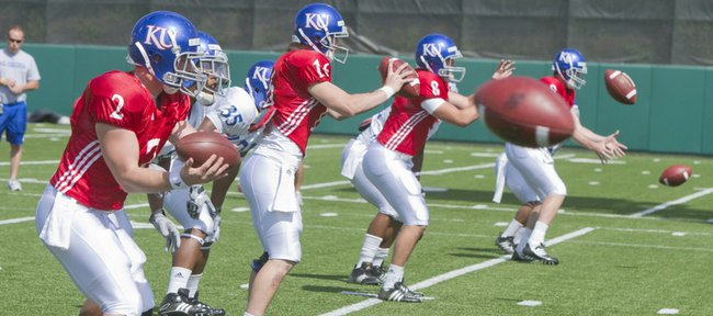 Kansas University quarterback Quinn Mecham (8) works on taking snaps, alongside Jordan Webb (2), Jacob Morse (16) and Conner Teahan, far right, on April 19 at a spring practice at Memorial Stadium. Turner Gill has options but has not named a starting quarterback for the game against Colorado.