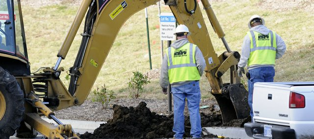 Black Hills Energy crews work to repair a gas line break Friday, Oct. 29, 2010 in the parking lot behind the School of Pharmacy building on Kansas University's West Campus.